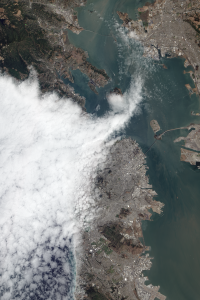 Fog squeezes through between San Francisco to the south and the Marin headlands to the north